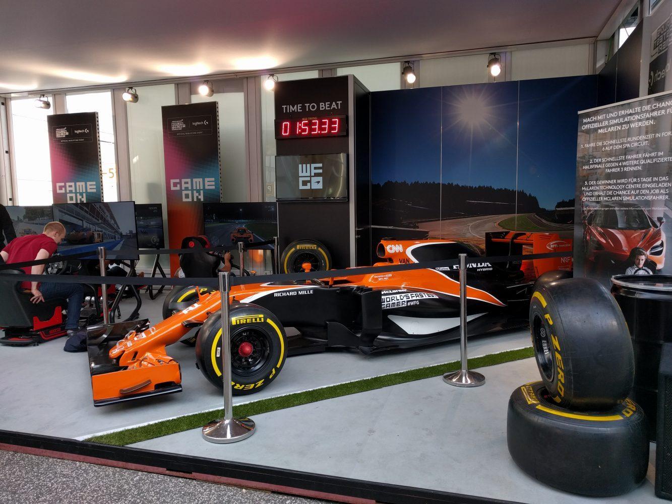 Links sind die Gaming-Setups bestehend aus Logitech-Lenkrädern, Sparco-Sitzen und PCs mit installiertem Forza 6 aufgebaut gewesen, rechts konnte man sich ein Formel-1 Promo-Auto von McLaren ansehen. (Foto: Hendrik Laudemann)